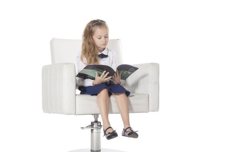 7 år gammalt flickasammanträde på en stol och en läsning som isoleras på vit bakgrund arkivfoto