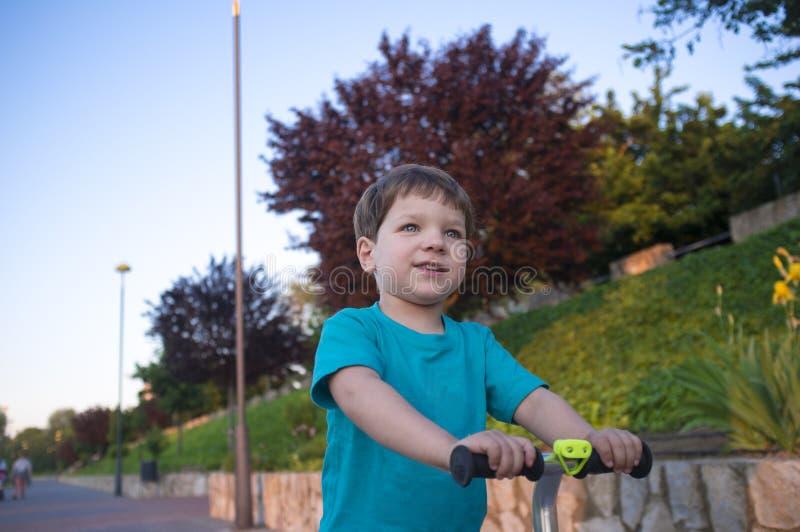 3 år pojke som rider en sparkcykel på staden, parkerar på solig vårdag arkivbilder