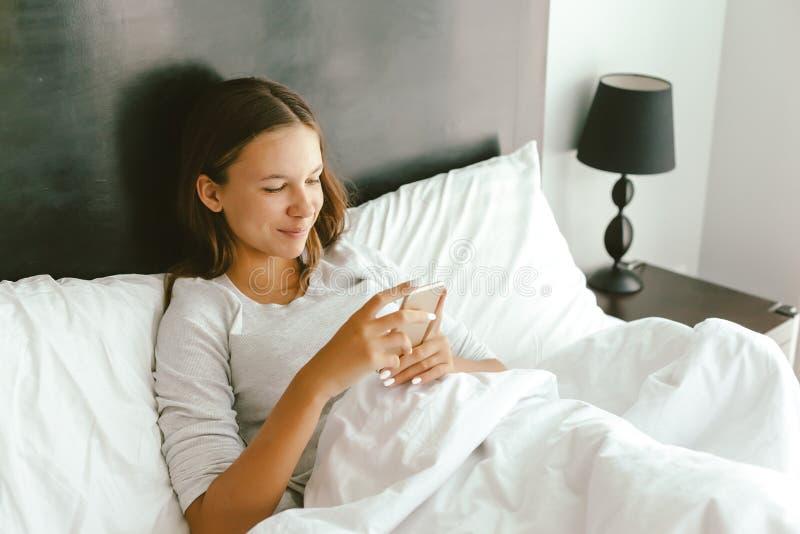 12-14 år teenagflicka som använder smartphonen i säng fotografering för bildbyråer