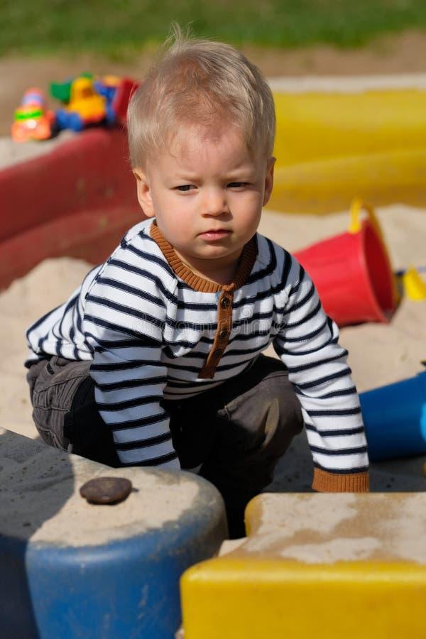 Årig en behandla som ett barn pojkelilla barnet på lekplatssandlådan royaltyfri bild