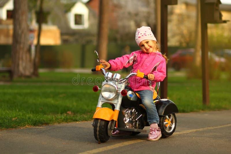 Årig flicka för innegrej som tre poserar på en cykel royaltyfri bild