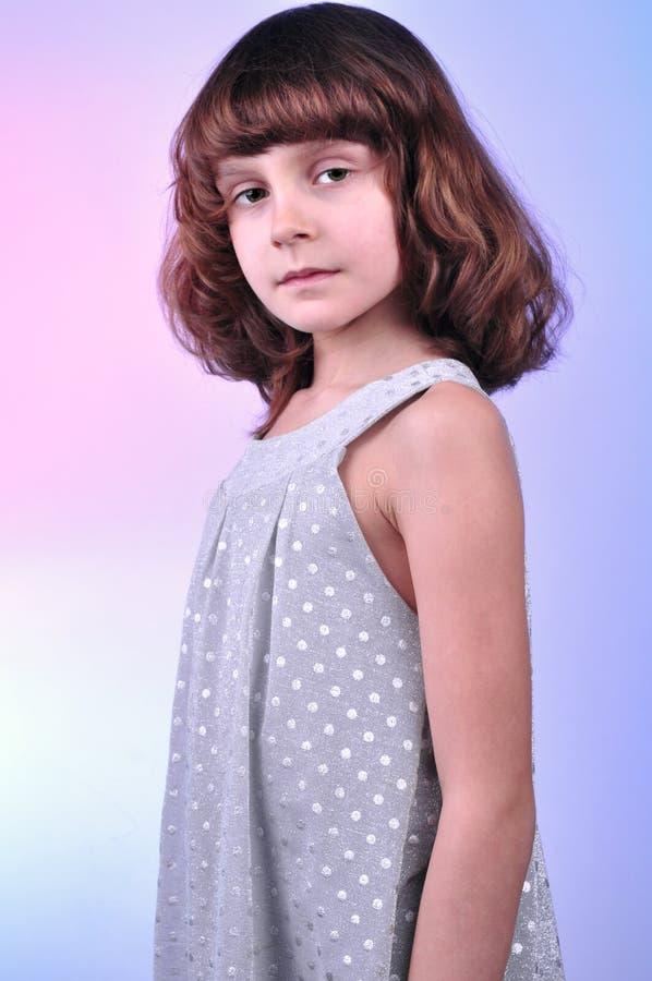Årig flicka nätta 8 i silverklänning fotografering för bildbyråer