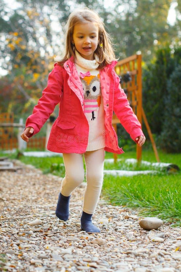årig flicka som 4 går över kiselstenar arkivbilder