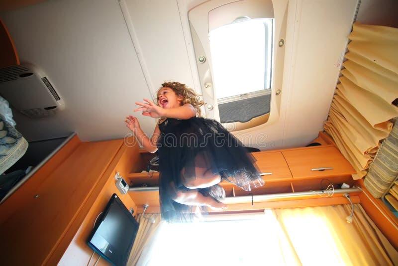 4-5 årig flicka som spelar att hoppa från en soffa till andra royaltyfri foto