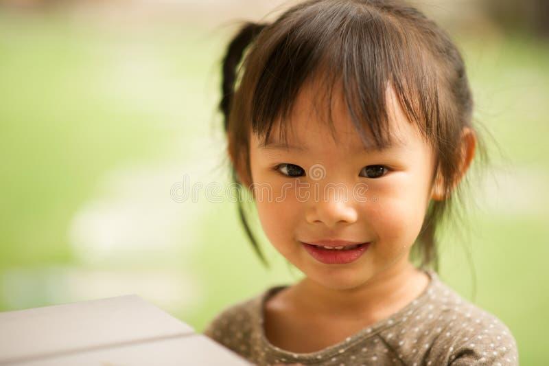 årig kinesisk asiatisk flicka 5 i trädgårds- le arkivfoto