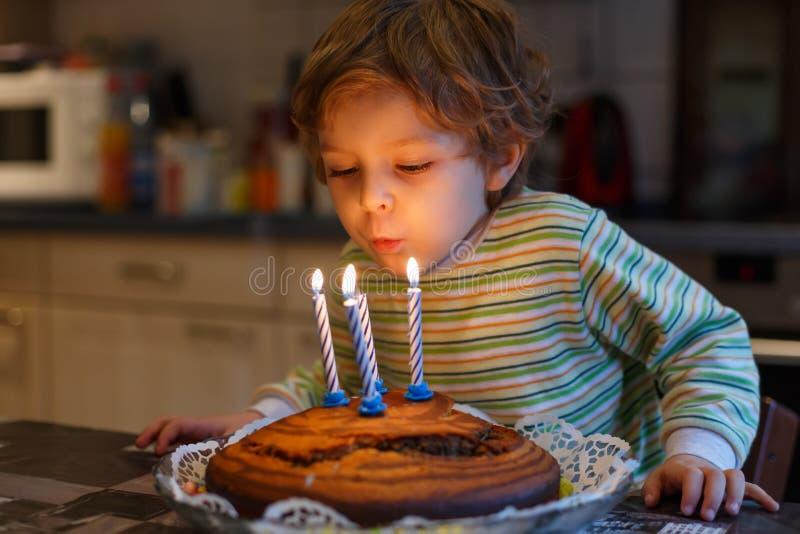 Årig pojke som förtjusande fyra firar hans födelsedag och blåsa royaltyfria foton