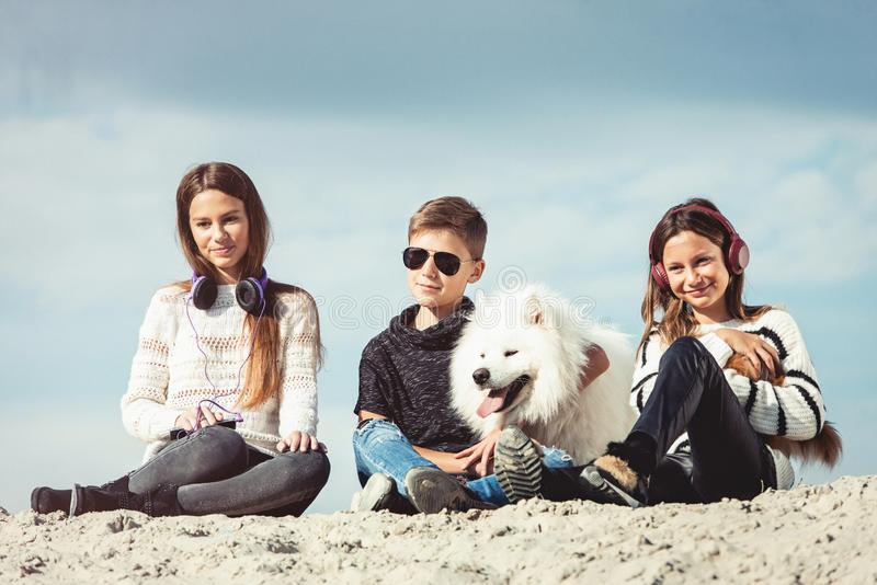 Årig pojke som lyckliga 11 kramar upp hans hundavelSamoyed på kusten mot ett slut för blå himmel Bästa vän vilar och arkivfoton