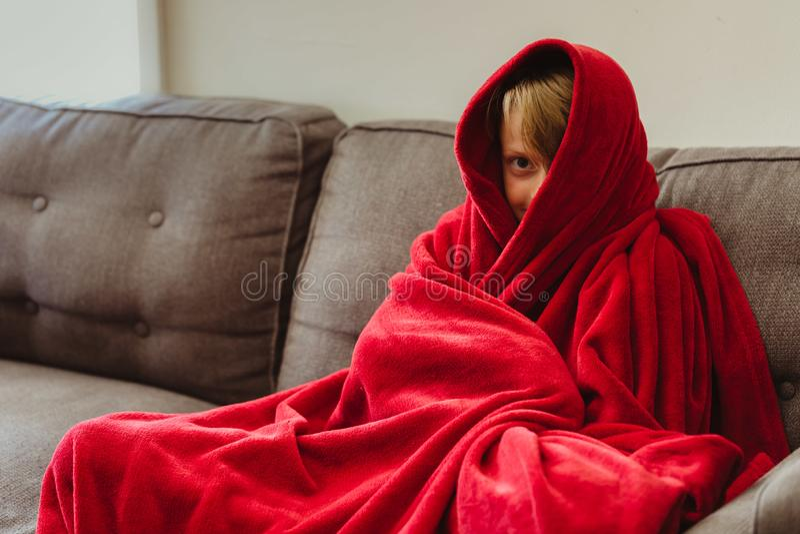 årig pojke som 8 sitter på en soffa med en röd filt royaltyfri foto