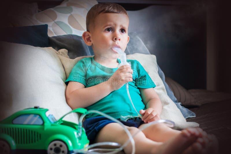 Årig pojke som tre hemma gör inandning med nebulizeren arkivfoto