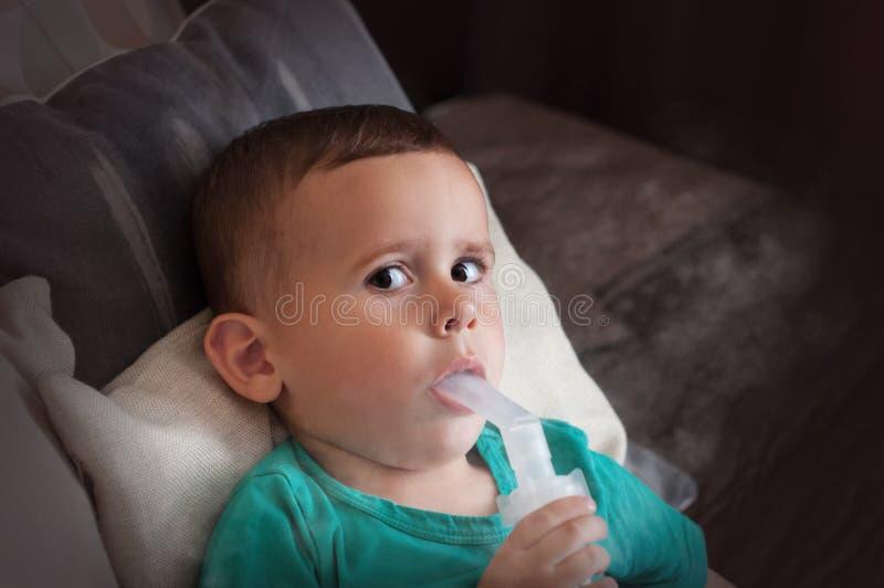 Årig pojke som tre hemma gör inandning med nebulizeren royaltyfria bilder
