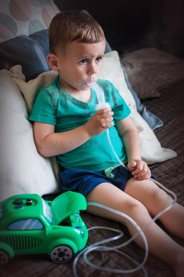Årig pojke som tre hemma gör inandning med nebulizeren arkivbilder