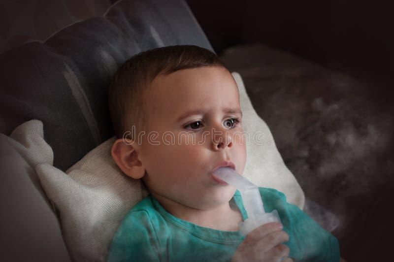 Årig pojke som tre hemma gör inandning med nebulizeren arkivfoton