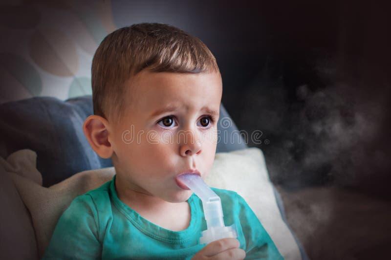 Årig pojke som tre hemma gör inandning med nebulizeren fotografering för bildbyråer