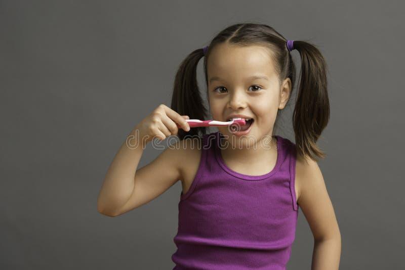 årig unge som 5 borstar hennes tänder arkivfoto