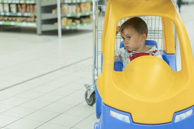 Åriga gulliga ledsna lite 2 behandla som ett barn pojkebarnet i den lilla leksak-bilen spårvagnen på supermarket, farsa eller upp royaltyfri bild