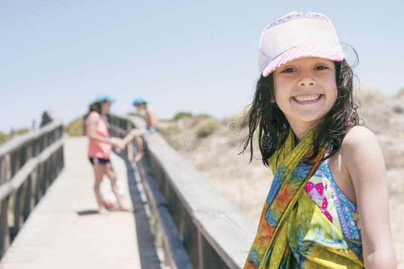 6 åriga liten flickablickar på kameran efter en dag av strandsemestrar som slås in i pareostund i bakgrunden hennes moder, fäster royaltyfria foton