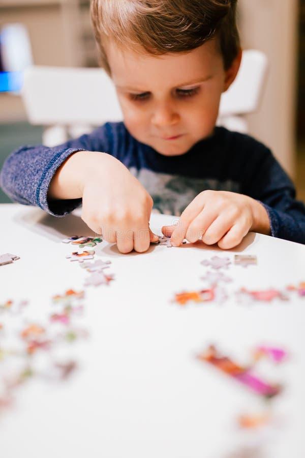 årigt barn som 2 löser pusslet royaltyfria bilder