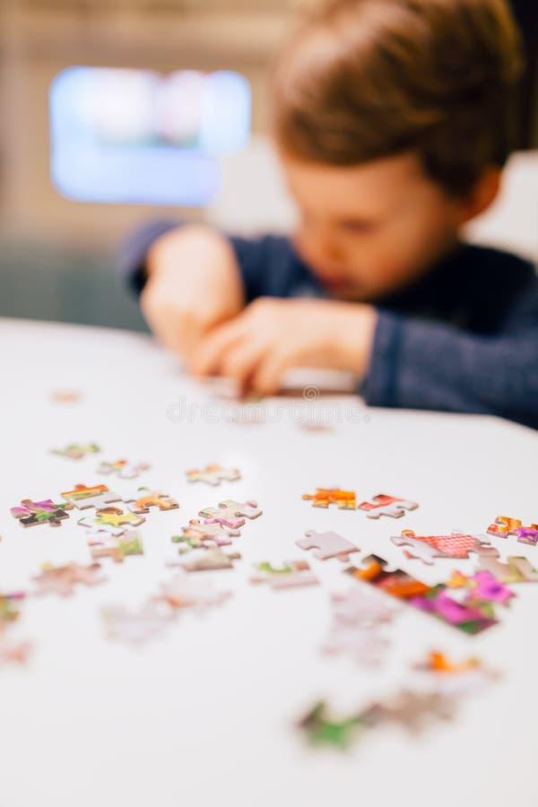 årigt barn som 2 löser pusslet royaltyfria foton