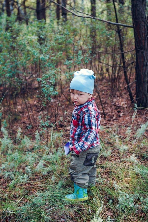 Årigt barn två i rrubberkängor i skogen royaltyfri fotografi