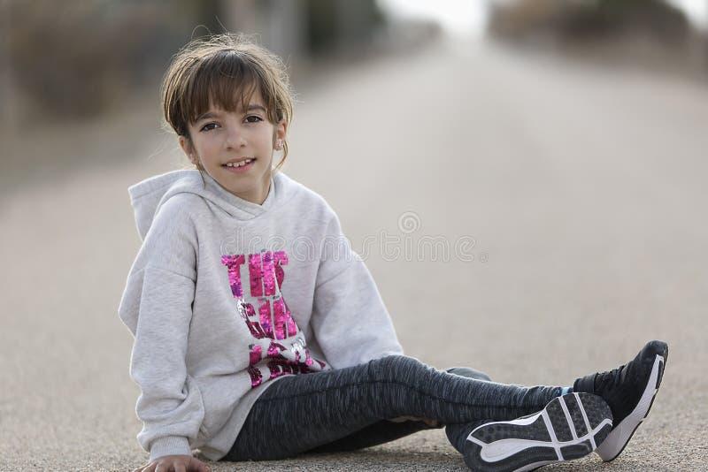 10-årigt flickasammanträde på golvet av en bil som ser caen royaltyfri foto