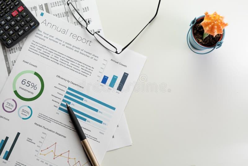 Årsrapportark med diagram, pennan, räknemaskinen, glasögon och kaktuns på vit royaltyfria foton