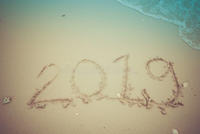 Årsslutbegrepp 2019, bokstäver för 2019 nummer på havsstranden, våg och guld- ljus av solnedgången royaltyfri fotografi