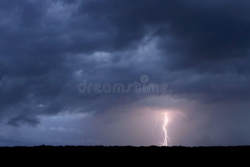 Åska och blixt i fältet. arkivfoton