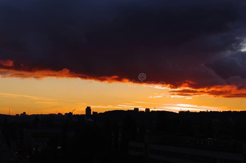 Åskmoln på den röda solnedgången i staden royaltyfri foto