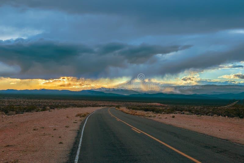 Åskväder över den tomma vägen i dalen av branddelstatsparken nevada USA fotografering för bildbyråer