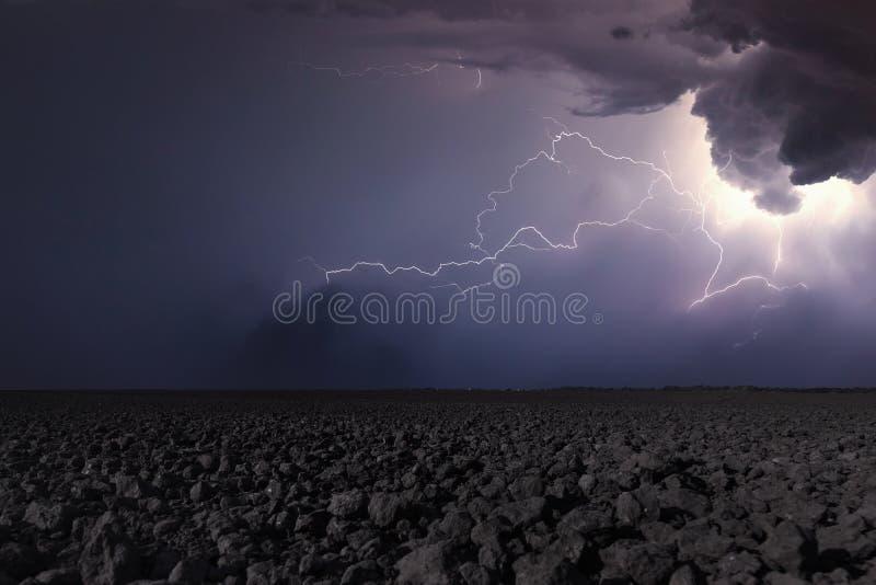 Åskväder med blixt i plogat fält Åskväderbackgr arkivbilder