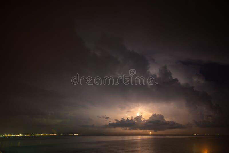Åskvädret över havet, blixt slår vattnet arkivbilder