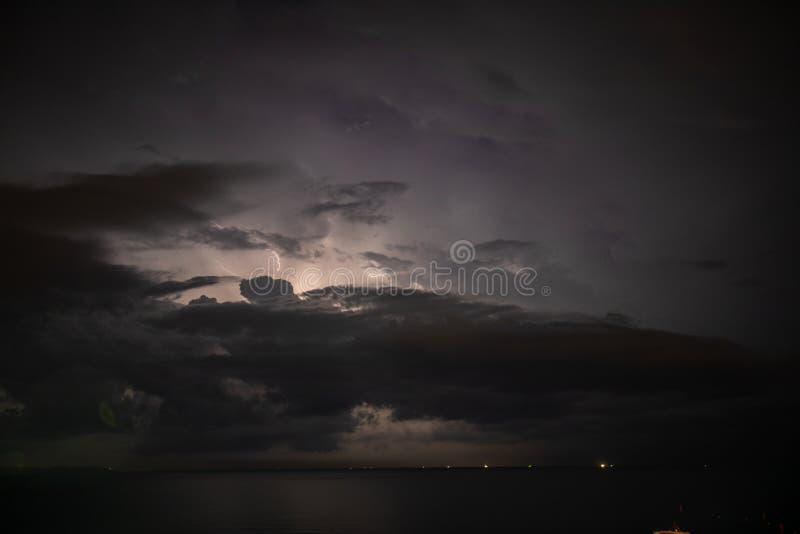 Åskvädret över havet, blixt slår vattnet arkivbild