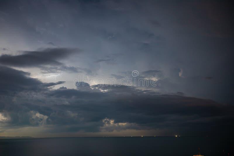 Åskvädret över havet, blixt slår vattnet arkivfoto