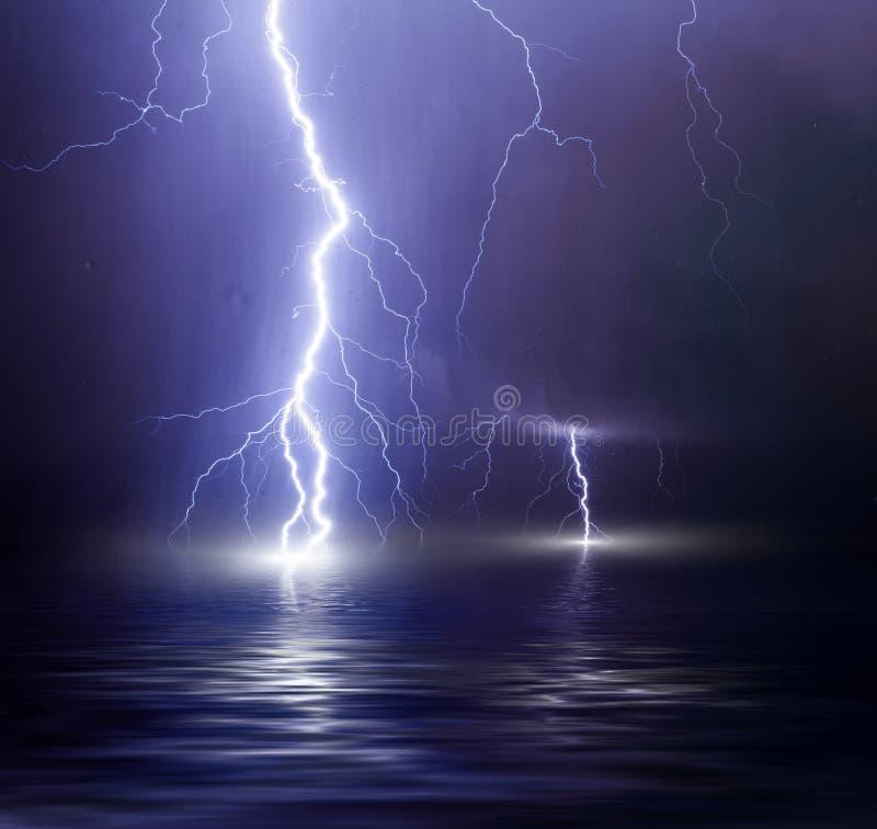Åskvädret över havet, blixt slår vattnet royaltyfri bild