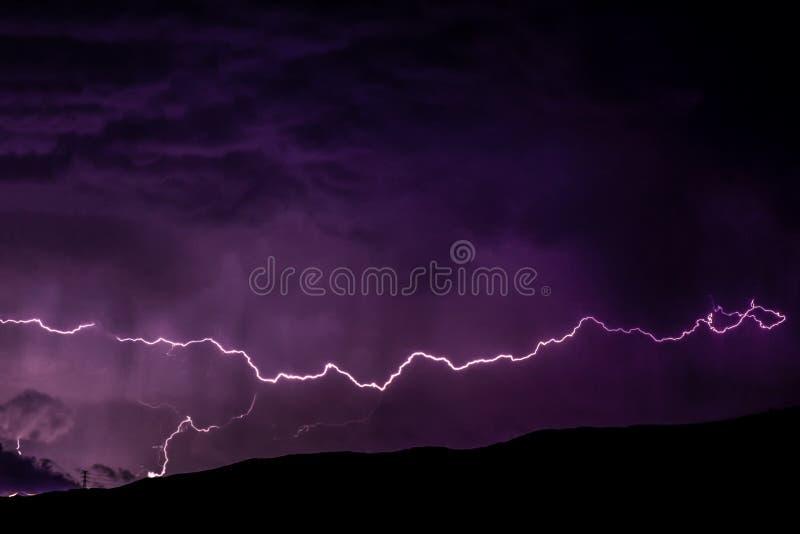 Åskvigg över bergen med det höga elektriska spänningstornet royaltyfri bild