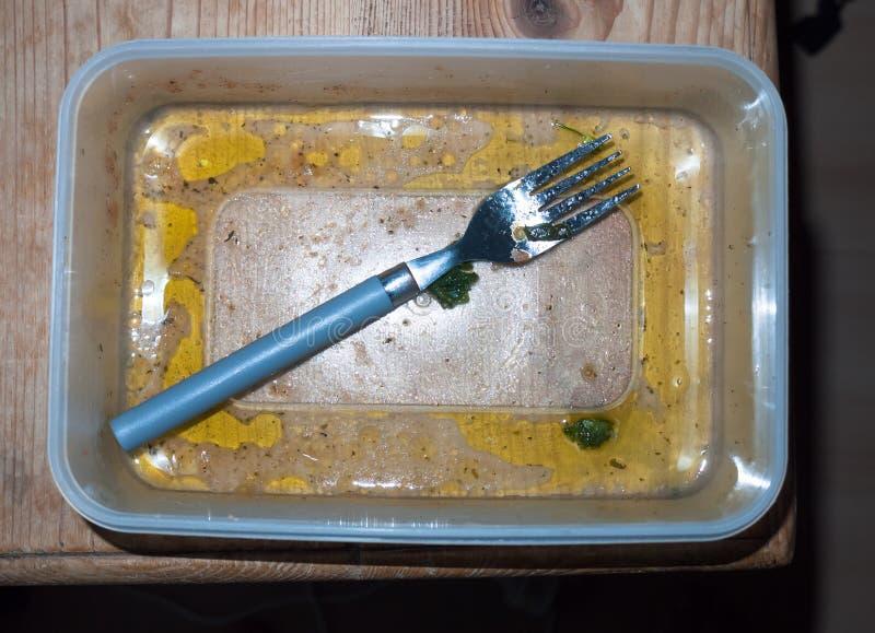 Åt rester och tomt orent för smutsig tupperware och för gaffel arkivfoton