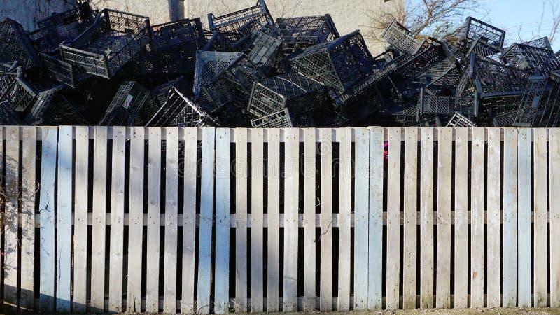 Återanvända plast- spjällådor bak det vita staketet arkivfoton