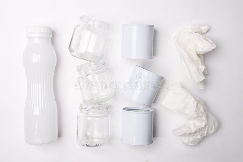 Återanvändbar avskräde som består av exponeringsglas, plast-, metall och papper på vit bakgrund Vitt texturbegrepp royaltyfri fotografi
