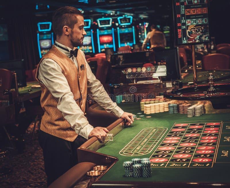 Återförsäljare bak tabellen i en kasino arkivfoto