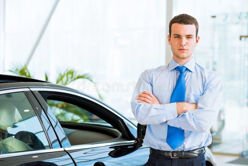 Återförsäljaren står nära en ny bil i visningslokalen royaltyfria bilder