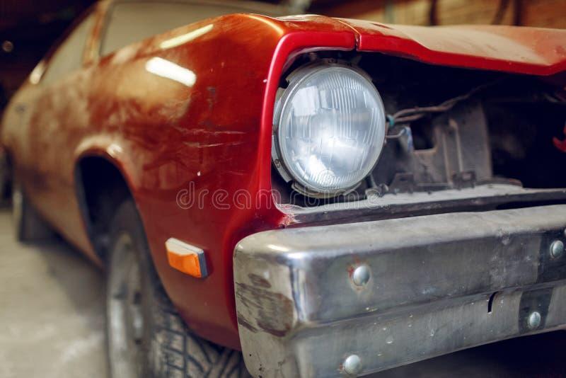 Återställande av den klassiska bilen Slut upp bilen för främre sida för sikt den klassiska, främre billykta av en bruten dammig b royaltyfri fotografi