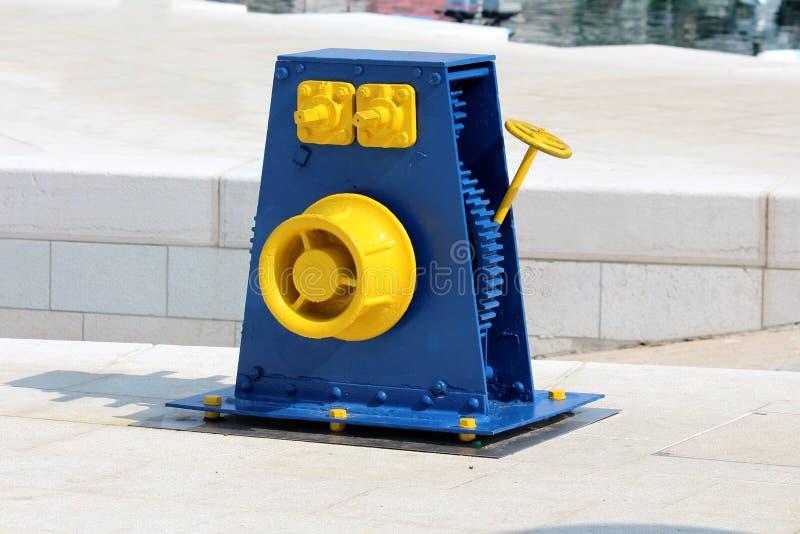 Återställt blått för tappning retro och gult gjutjärnblockhjul som monteras på den traditionella stentegelplattapir som används f royaltyfri bild
