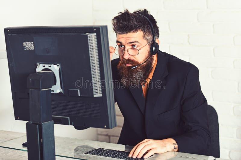 Återstå artigt och rimligt Skäggig företagsrepresentant på datoren Center operatör för ett felanmälan Skäggigt manarbete royaltyfri foto