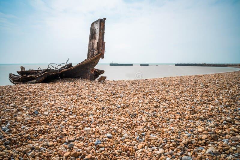 Återstår en gammal träfiskebåt på den steniga stranden i Hastings, E arkivbild