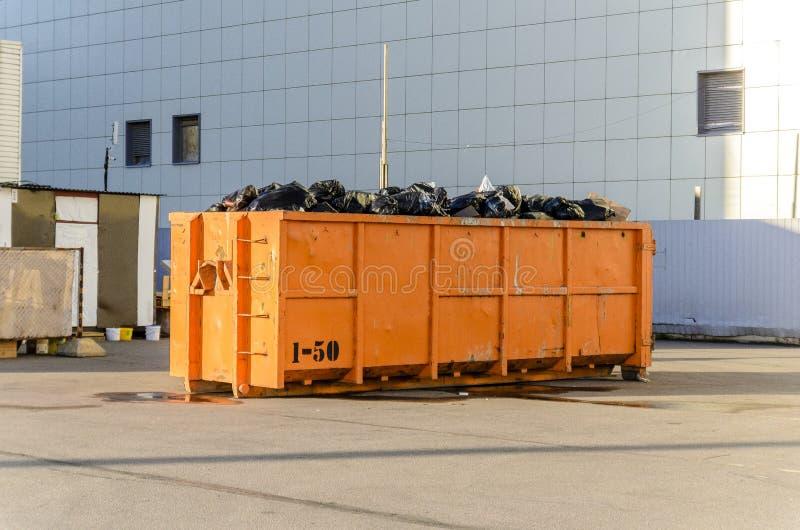 Återvinning av avskräde och avfalls, en stor orange behållare för avfalls av en bestämd kategori a royaltyfri foto