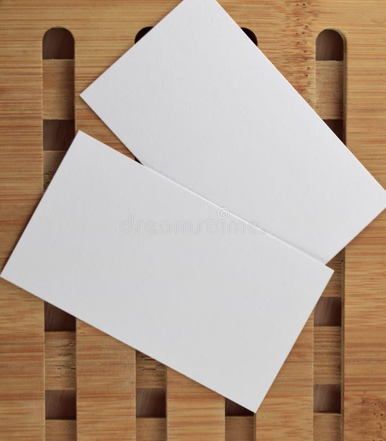 Åtlöje för affärskort upp för presentationer och portföljer Mallmodell för att brännmärka identitet Tomma vita affärskort på trä arkivbilder