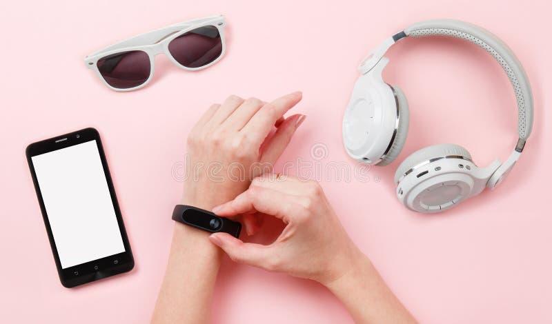 Åtlöje för bästa sikt upp med konditionbogseraren förestående, telefon, hörlurar, exponeringsglas på rosa bakgrund royaltyfri fotografi