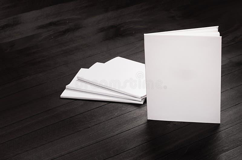 Åtlöje för företags identitet upp av tomma tidskrifter som står på svart stilfull wood bakgrund, mall royaltyfri bild