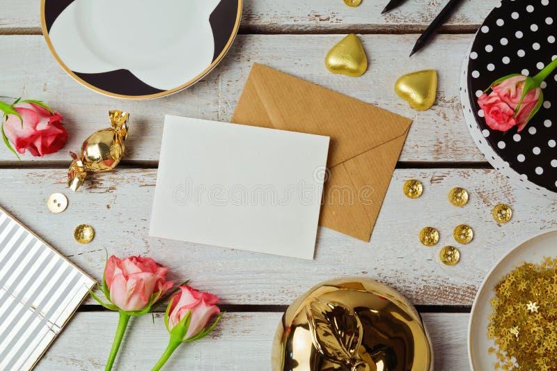 Åtlöje för hälsningkort upp mall med steg blommor och choklader på träbakgrund ovanför sikt royaltyfri foto