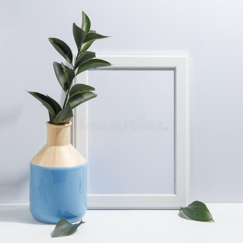 Åtlöje upp den vita ramen och filial med gröna sidor i blå vas på det bokhylla eller skrivbordet Minimalistic begrepp royaltyfria foton